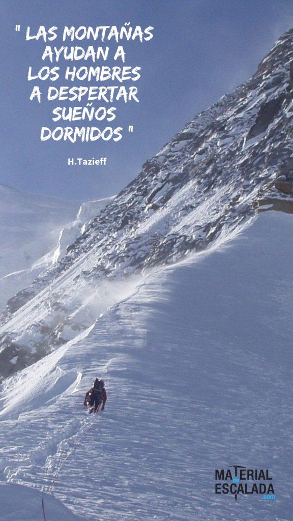 Vista de un alpinista en la divisoria de la montaña nevada. Contrasta con le cielo azul y la nieve con los tonos gris oscuro de la roca.
