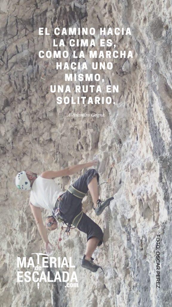 Escalador con casco visionando el siguiente paso, agarrado con una sola mano, pared de roca caliza con tonos marrones y grises